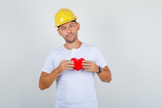 Строитель мужчина держит красное сердце в белой футболке, шлеме и выглядит счастливым, вид спереди