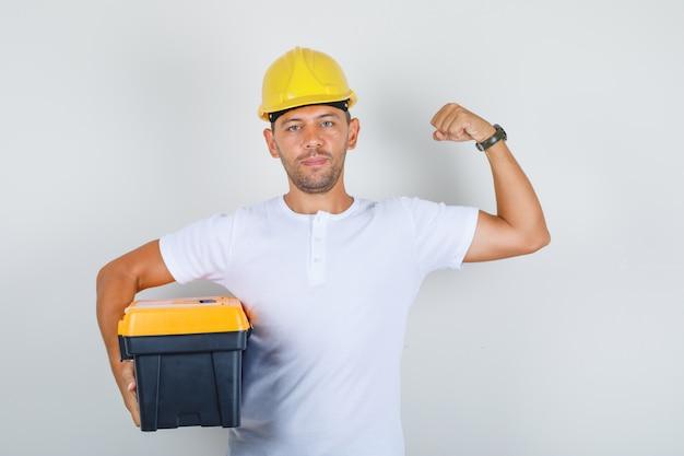 Строитель мужчина держит ящик для инструментов и показывает мышцы в футболке, шлеме и выглядит уверенно, вид спереди.