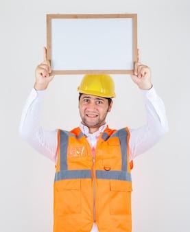 Uomo del costruttore che tiene il bordo bianco sopra la testa in camicia, uniforme e che sembra allegro, vista frontale.