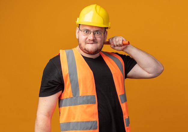 Человек-строитель в строительном жилете и защитном шлеме с молотком смотрит в камеру с сердитым лицом