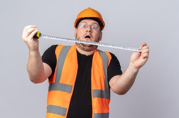 건설 조끼와 안전 헬멧을 쓴 빌더 남자는 흰색 배경 위에 놀라고 놀란 것처럼 보이는 측정 테이프를 들고 있다