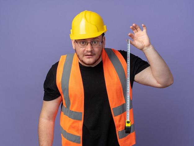 건설 조끼와 안전 헬멧에 작성기 남자가 놀란 카메라를보고 측정 테이프를 들고