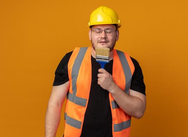 마이크 노래처럼 그것을 사용하여 페인트 브러시를 들고 건설 조끼와 안전 헬멧에 작성기 남자