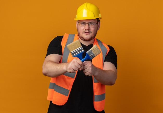 Человек-строитель в строительном жилете и защитном шлеме, держащий кисти, смотрит в камеру с уверенным выражением лица