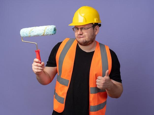 건설 조끼를 입은 빌더 남자와 파란색 배경 위에 서 있는 엄지손가락을 보여주는 카메라를 바라보는 페인트 롤러를 들고 있는 안전 헬멧