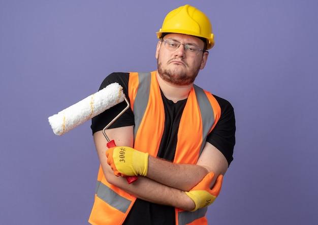 심각한 자신감 표정으로 카메라를보고 페인트 롤러를 들고 건설 조끼와 안전 헬멧에 작성기 남자