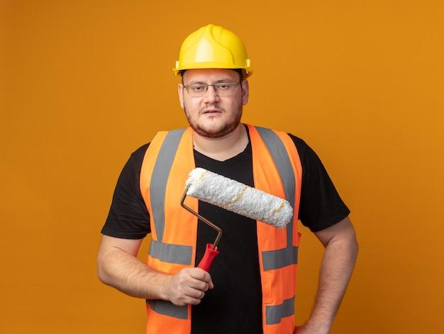 심각한 얼굴로 카메라를보고 페인트 롤러를 들고 건설 조끼와 안전 헬멧에 작성기 남자
