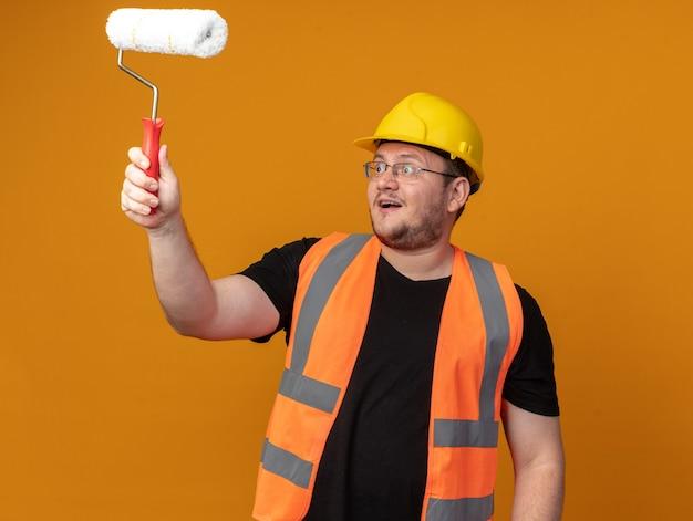 Человек-строитель в строительном жилете и защитном шлеме, держащий валик с краской, смотрит на него с удивлением и счастьем, стоя на оранжевом фоне