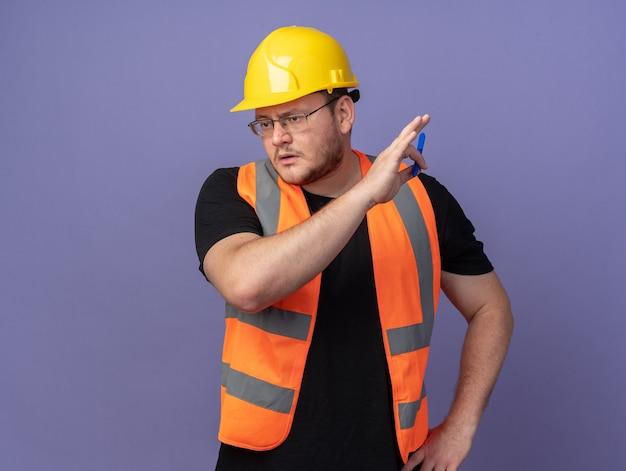 건설 조끼와 안전 헬멧에 작성기 남자 파란색 위에 서 심각한 얼굴로 옆으로 찾고 펜을 들고