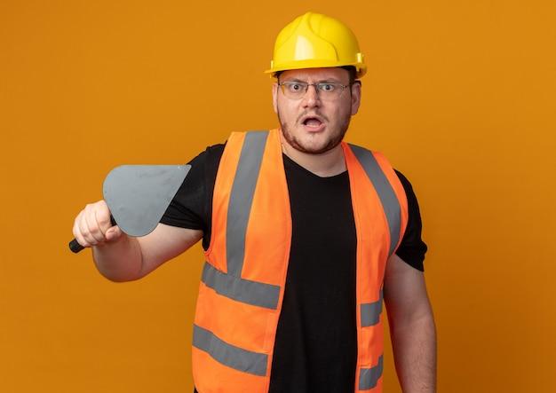 건설 조끼를 입은 빌더 남자와 퍼티 나이프를 들고 카메라를 바라보는 안전 헬멧이 주황색 배경 위에 서 있는 화난 얼굴에 불만을 품고 있다