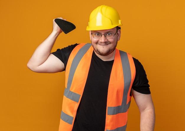 건설 조끼와 안전 헬멧에 작성기 남자 행복 한 얼굴로 웃 고 카메라를 찾고 퍼티 나이프를 들고