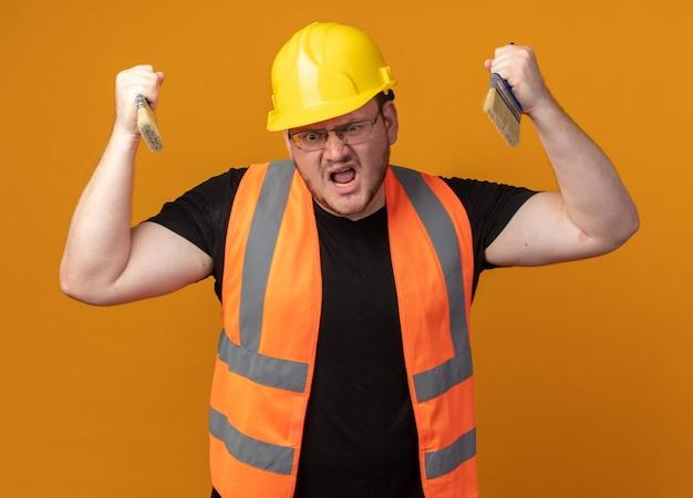 Строитель в строительном жилете и защитном шлеме держит две кисти и кричит с агрессивным выражением лица