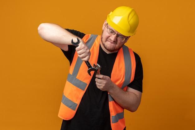 건설 조끼와 안전 헬멧 작성기 남자는 오렌지 위에 서서 혼란스럽고 불쾌한 찾고 두 렌치를 들고