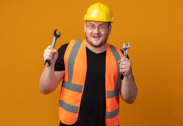 건설 조끼와 안전 헬멧을 쓴 빌더 남자는 주황색 배경 위에 서 있는 카메라를 보고 행복하고 놀란다