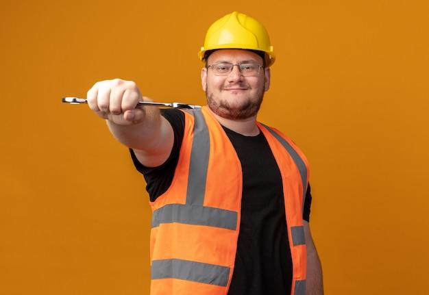 건설 조끼와 안전 헬멧에 렌치를 들고 있는 빌더 남자는 주황색 배경 위에 서 있는 얼굴에 자신감 있는 미소로 카메라를 바라보고 있습니다.
