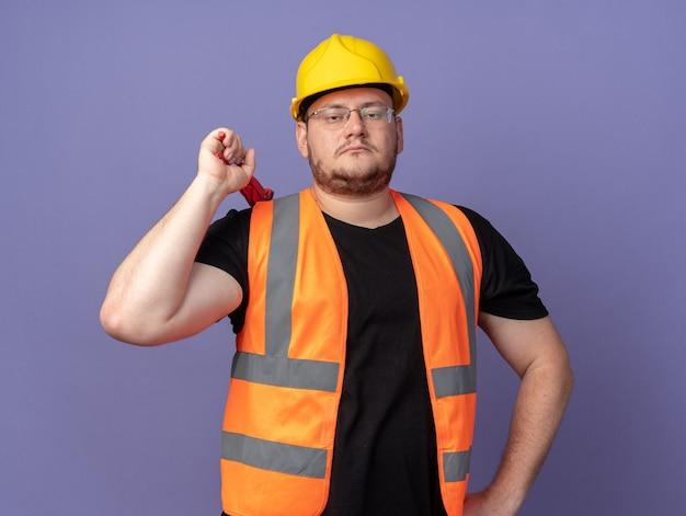 青の上に立っている真剣な自信を持ってカメラを見てレンチを保持している建設ベストと安全ヘルメットのビルダーの男