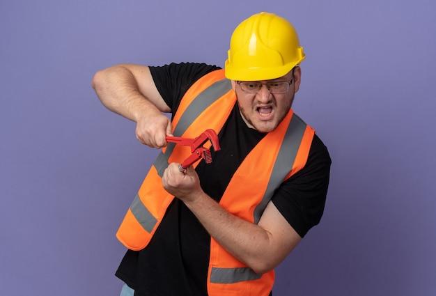 感情的で心配そうに見えるレンチを保持している建設ベストと安全ヘルメットのビルダーの男