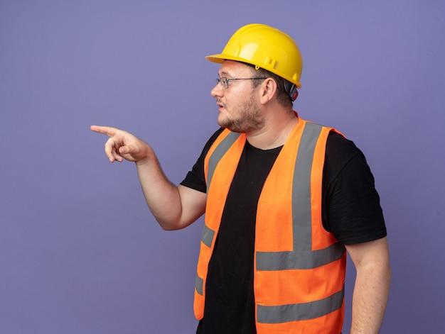 건설 조끼와 안전 헬멧 작성기 남자 옆으로 검지 손가락으로 가리키는 심각한 얼굴로 옆으로 찾고