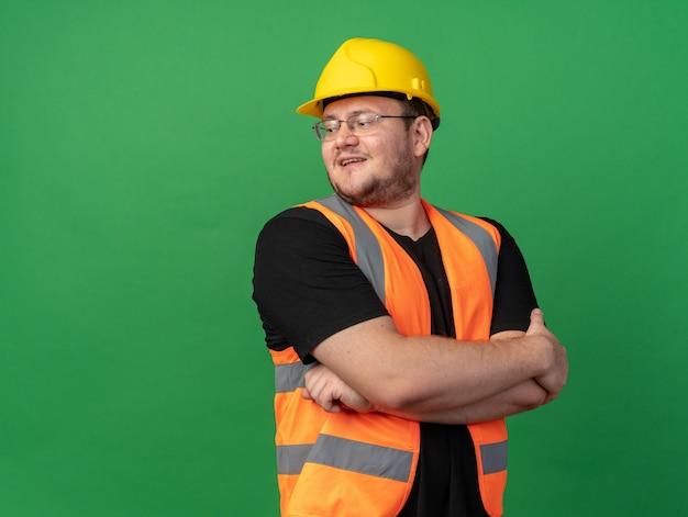 Строитель в строительном жилете и защитном шлеме смотрит в сторону с улыбкой на лице со скрещенными руками