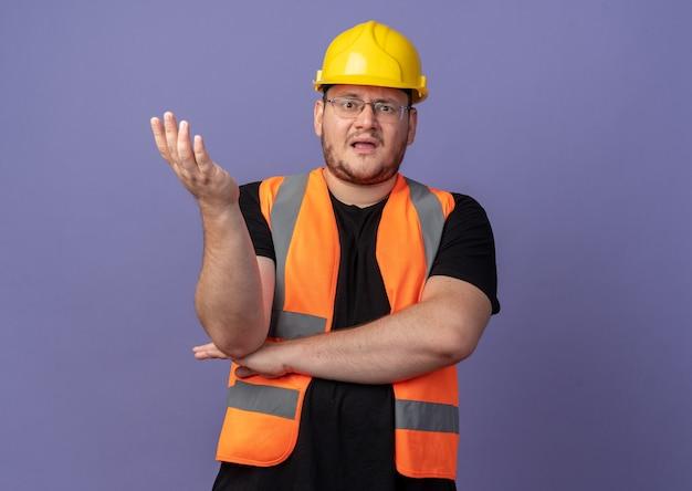건설 조끼와 안전 헬멧 작성기 남자 카메라를보고 혼란스럽고 파란색 위에 서있는 논쟁으로 팔로 불쾌감을 느낍니다.