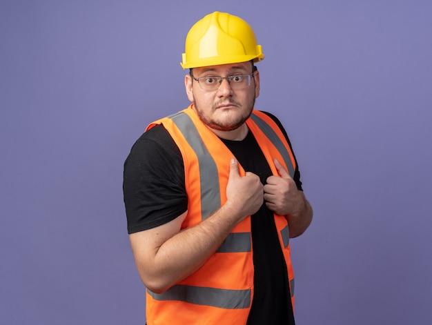 건설 조끼와 안전 헬멧 작성기 남자 카메라를보고 혼란과 파란색 위에 서 걱정