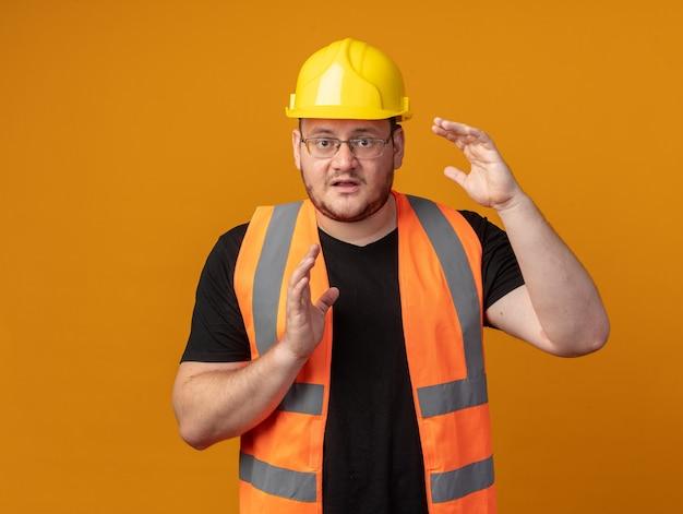 Человек-строитель в строительном жилете и защитном шлеме, смущенно глядя в камеру, показывает жест размера с обеспокоенными руками, стоя на оранжевом фоне
