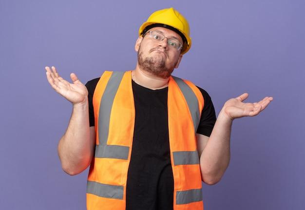 건설 조끼와 안전 헬멧을 쓴 빌더 남자는 파란 배경 위에 서서 대답이 없는 어깨를 으쓱하며 혼란스러워하는 카메라를 바라보고 있다
