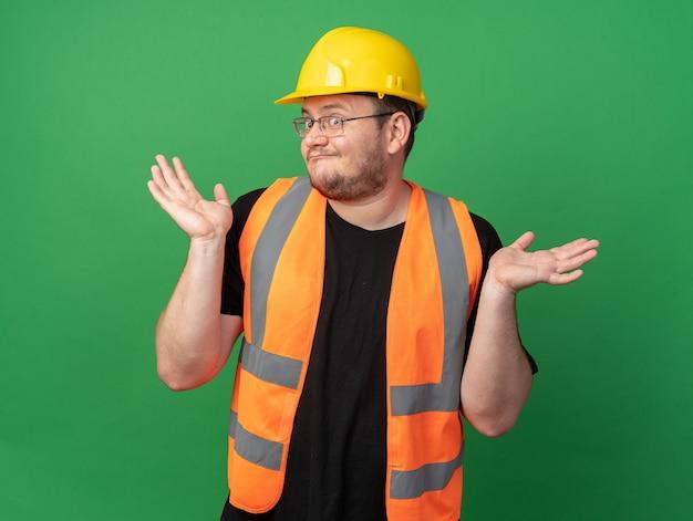 건설 조끼와 안전 헬멧을 쓴 빌더 남자가 카메라를 쳐다보며 혼란스러워 팔을 옆으로 벌리고 녹색 배경 위에 서 있는 대답이 없다