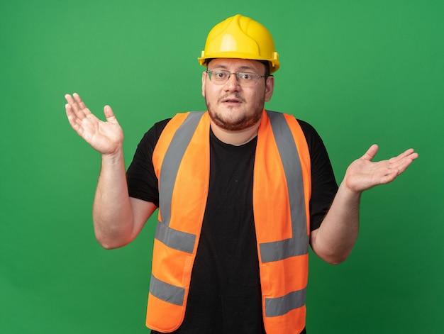 Человек-строитель в строительном жилете и защитном шлеме, смотрящий в камеру, смущенно разводит руки в стороны, не имея ответа, стоя на зеленом фоне