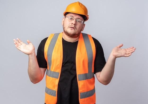 건설 조끼와 안전 헬멧을 쓴 빌더 남자는 카메라를 쳐다보며 혼란스러워 팔을 옆으로 벌리고 흰색 배경 위에 서 있는 대답이 없다