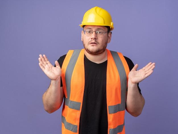 건설 조끼 및 안전 헬멧 작성기 남자 카메라를보고 파란색 위에 서있는 측면에 팔을 확산 혼란