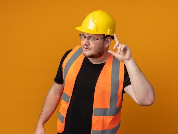 건설 조끼와 안전 헬멧을 쓴 빌더 남자는 주황색 배경 위에 서 있는 그의 사원에서 검지 손가락으로 가리키는 카메라를 보고 있습니다.