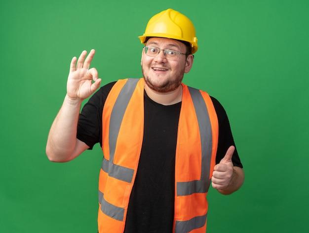 건설 조끼와 안전 헬멧을 쓴 빌더 남자는 녹색 배경 위에 서 있는 엄지손가락을 보여주는 확인 표시를 하면서 즐겁게 웃고 있는 카메라를 바라보고 있습니다.