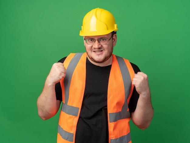 건설 조끼와 안전 헬멧을 쓴 빌더 남자는 녹색 배경 위에 자신감 있고 행복하고 긍정적인 미소를 지으며 카메라를 바라보고 있습니다
