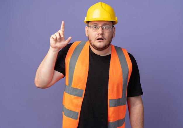 건설 조끼와 안전 헬멧 작성기 남자 카메라를보고 놀라게하고 파란색 위에 서있는 검지 손가락을 보여주는 걱정