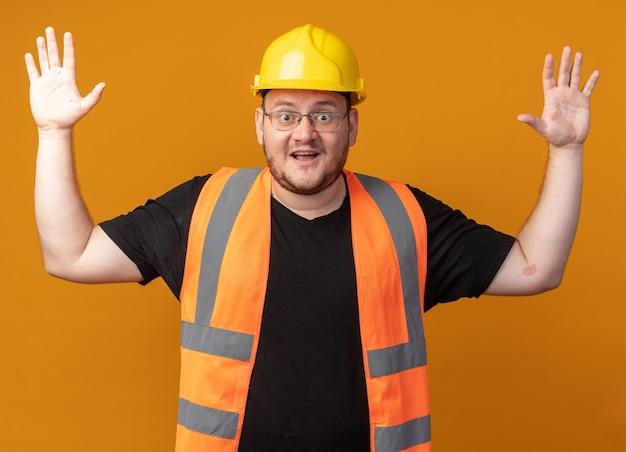 건설 조끼와 안전 헬멧을 쓴 빌더 남자가 주황색 배경 위에 서 있는 팔을 들고 놀란 카메라를 보고 있다