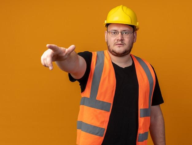 건설 조끼와 안전 헬멧을 쓴 빌더 남자는 주황색 배경 위에 서 있는 무언가를 검지 손가락으로 가리키는 심각한 얼굴로 카메라를 쳐다보고 있습니다.