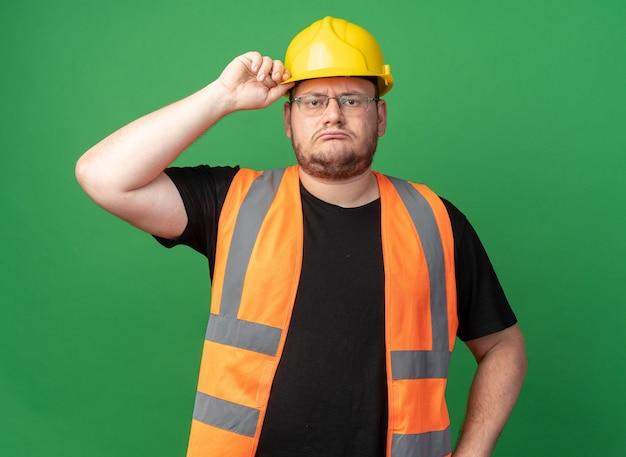 건설 조끼와 안전 헬멧을 쓴 빌더 남자는 녹색 배경 위에 서 있는 헬멧을 만지는 심각한 얼굴로 카메라를 바라보고 있습니다.