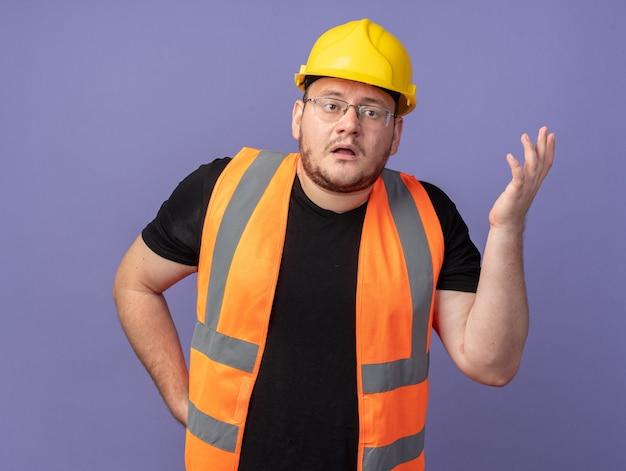 건설 조끼와 안전 헬멧을 쓴 빌더 남자는 파란색 배경 위에 불만과 분노로 팔을 들고 혼란스럽고 불쾌해 보입니다.