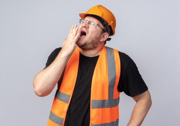 건설 조끼와 안전 헬멧에 작성기 남자 피곤하고 과로 하품 서 화이트 이상 찾고