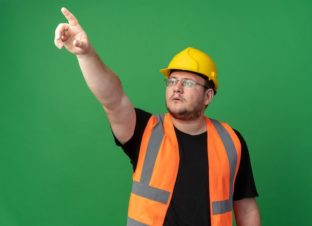 녹색 배경 위에 서 있는 무언가를 검지 손가락으로 가리키는 심각한 얼굴로 올려다보는 건설 조끼와 안전 헬멧을 쓴 빌더 남자