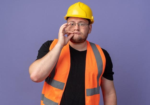 건설 조끼와 안전 헬멧을 쓴 빌더 남자는 파란색 배경 위에 지퍼가 서 있는 입을 닫는 것처럼 손가락으로 침묵 제스처를 취합니다.