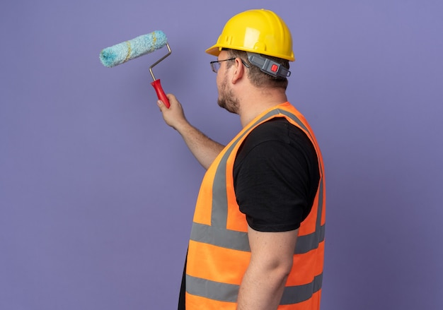 Человек-строитель в строительном жилете и защитном шлеме рисует стену с малярным валиком, стоящим на синем фоне