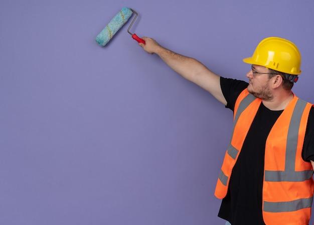 파란색 배경 위에 페인트 롤러가 서 있는 벽을 칠하는 건설 조끼와 안전 헬멧을 쓴 빌더 남자