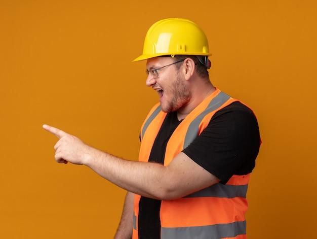 건설 조끼와 안전 헬멧을 쓴 빌더 남자는 검지 손가락으로 옆을 가리키며 주황색 배경 위에 서 있는 공격적인 표정으로 외치고 있다