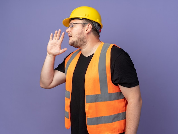 Человек-строитель в строительном жилете и защитном шлеме кричит рукой возле рта, стоя на синем фоне