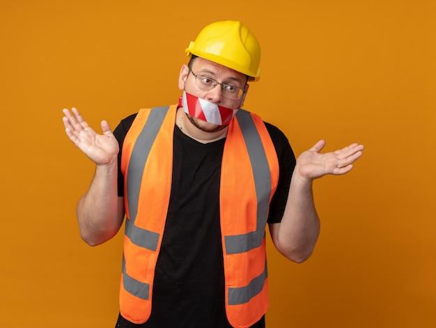 그의 입에 테이프와 건설 조끼와 안전 헬멧에 작성기 남자는 측면에 팔을 확산 혼란 찾고