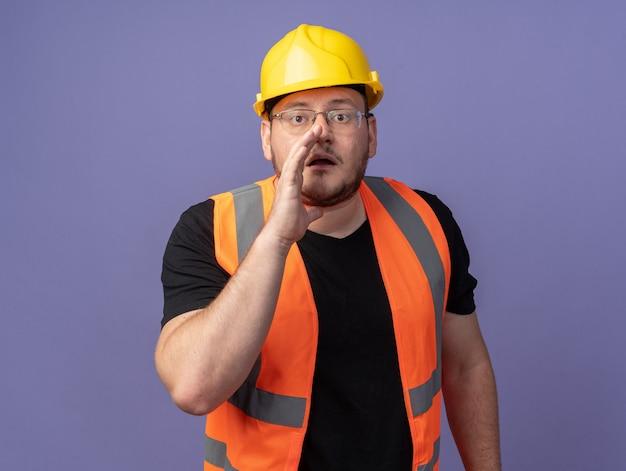建設ベストと安全ヘルメットのビルダーの男が口の近くで手で秘密をささやく