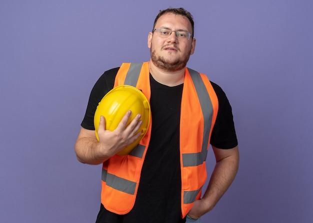 自信を持って笑顔のカメラを見て安全ヘルメットを保持している建設ベストのビルダー男