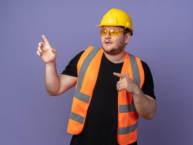 建設中のビルダーの男性は、黄色の安全メガネと安全ヘルメットを人差し指で何かを指差して混乱しているように見えます